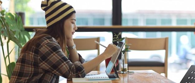 Vista lateral de la adolescente que trabaja con tableta digital en la mesa de madera con taza de café y jarrón de plantas