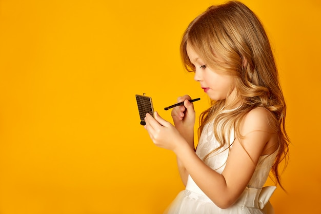 Vista lateral de la adorable niña con espejo de bolsillo y aplicar maquillaje mientras está de pie en la pared amarilla
