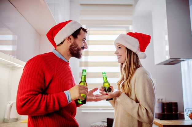 Vista lateral de la adorable pareja con sombreros de santa en las cabezas de pie en la cocina, hablando y bebiendo cerveza