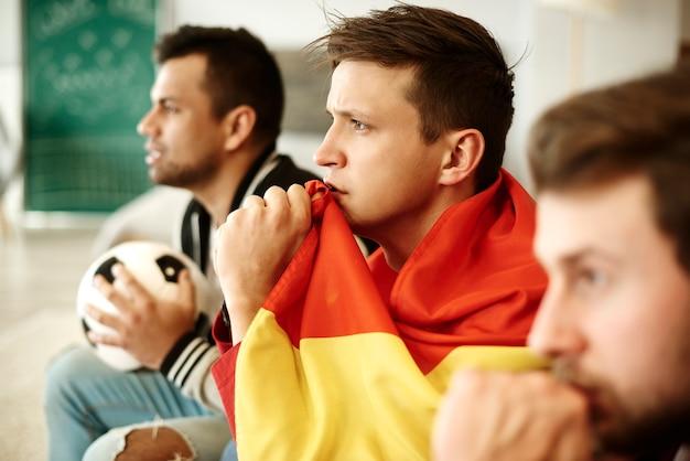 Vista lateral de los aficionados al fútbol rezando en casa