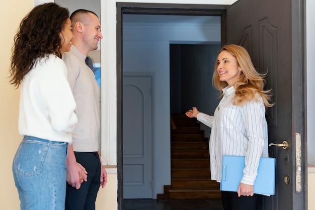 Vista lateral del agente de bienes raíces femenino invitando a la pareja a ver la nueva casa