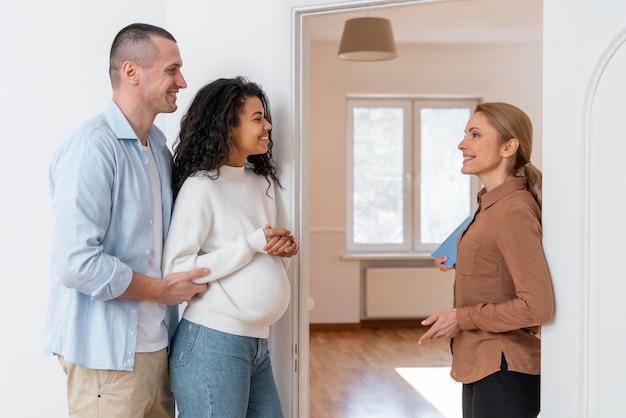 Vista lateral del agente de bienes raíces invitando a la pareja a ver la nueva casa