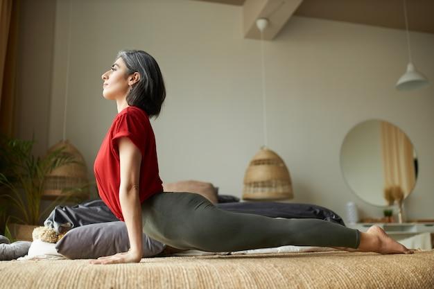 Vista lateral del ajuste muscular joven mujer de pelo gris practicando yoga en el dormitorio, haciendo pose de perro boca arriba
