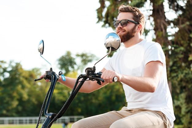 Vista lateral del alegre hombre con barba en gafas de sol paseos en moto moderna al aire libre y mirando a otro lado