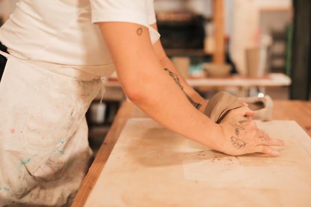 Vista lateral de un alfarero femenino amasando la masa en una mesa de madera