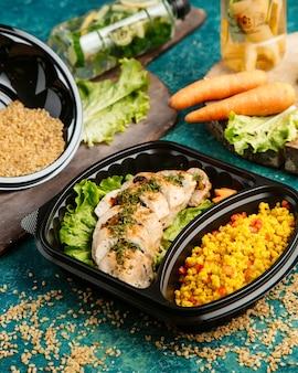 Vista lateral de alimentos dietéticos pechuga de pollo al horno sobre lechuga con mijo y tomates picados
