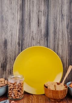 Vista lateral de almendras en un frasco de vidrio y un tazón con mantequilla de maní con una placa de cerámica amarilla sobre la mesa en el fondo de madera