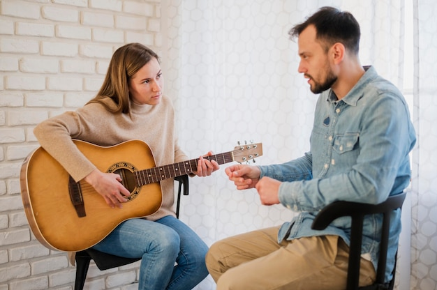 Vista lateral del alumno y profesor de guitarra en casa
