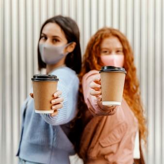 Vista lateral de amigas desenfocadas con máscaras faciales al aire libre sosteniendo tazas de café
