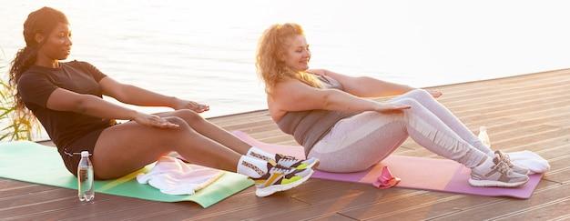 Vista lateral de amigas haciendo abdominales junto al lago