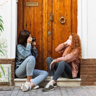 Vista lateral de amigas con máscaras faciales tomando fotografías con cámara