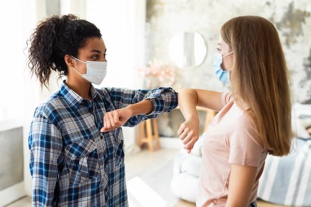 Vista lateral de amigas con máscaras médicas practicando el saludo del codo