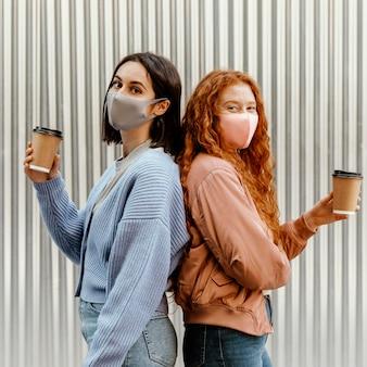 Vista lateral de amigas con mascarillas al aire libre sosteniendo tazas de café