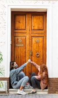 Vista lateral de amigas con mascarillas sentado junto a la puerta