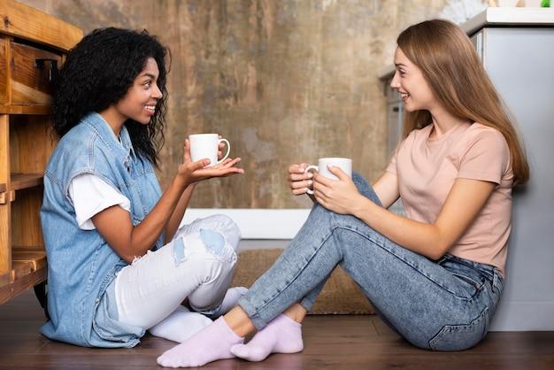 Vista lateral de amigas tener una conversación tomando un café