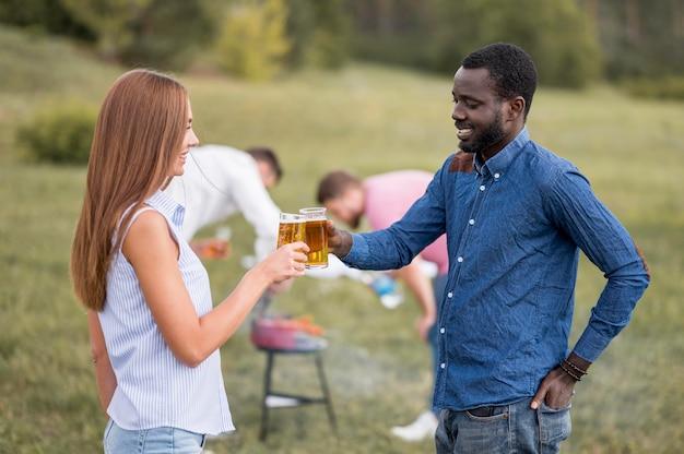 Vista lateral de amigos brindando con cerveza en una barbacoa