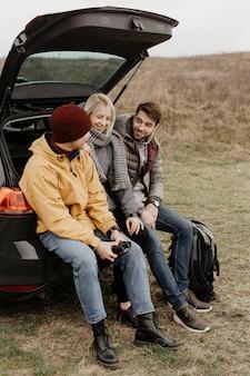 Vista lateral amigos sentados en el auto