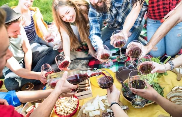 Vista lateral de amigos sirviendo y tostando copas de vino tinto.