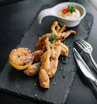 Vista lateral ancas de rana rebozadas con una rodaja de limón y salsa