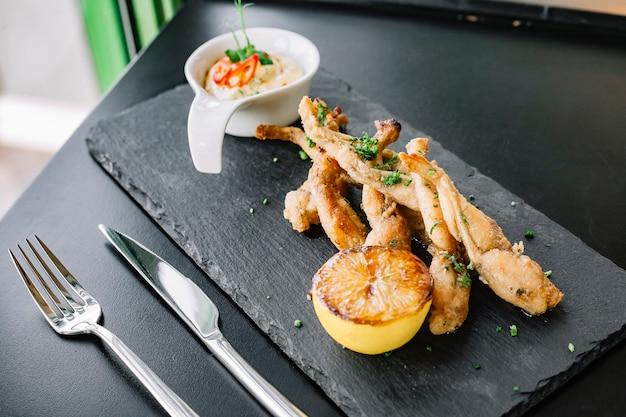 Vista lateral ancas de rana rebozadas con salsa y limón en una bandeja