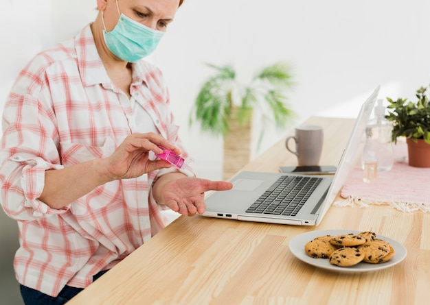 Vista lateral de la anciana desinfectando sus manos antes de usar la computadora portátil