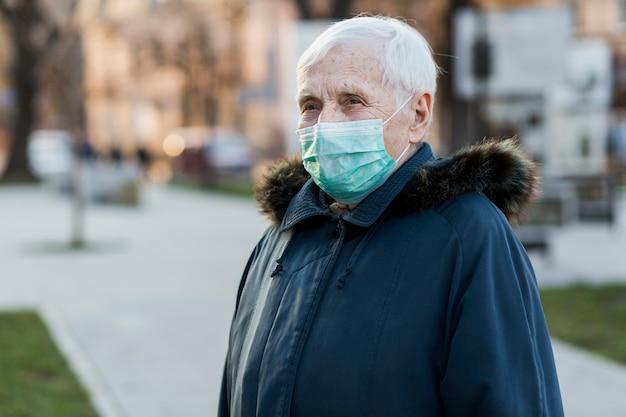 Vista lateral de la anciana con máscara médica en la ciudad