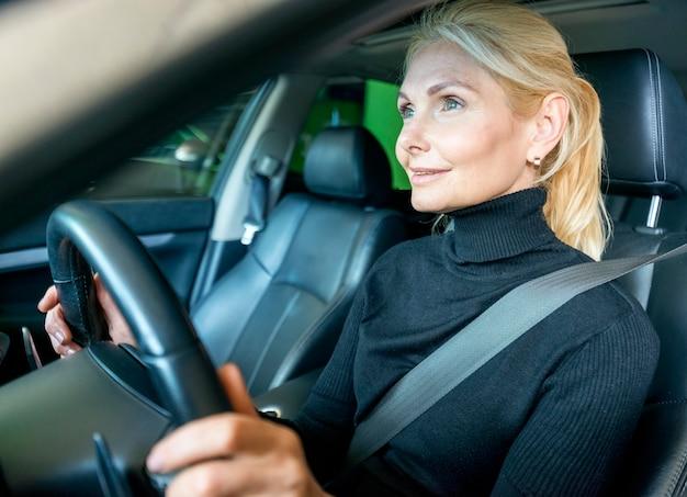 Vista lateral de la anciana mujer de negocios en coche