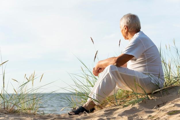 Vista lateral del anciano admirando la vista de la playa