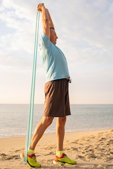 Vista lateral del anciano trabajando con cuerda elástica en la playa