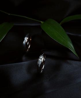 Vista lateral de anillos de bodas de plata en pared negra