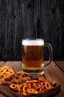 Vista lateral aperitivos para cerveza chips duras y mini brezel con jarra de cerveza en la mesa de madera