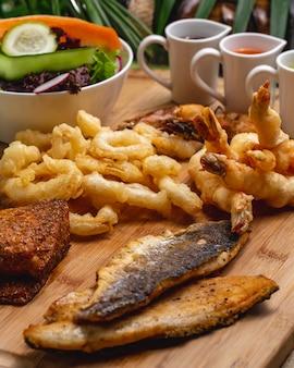 Vista lateral aperitivos de mariscos pescado camarones calamares con salsas y ensalada