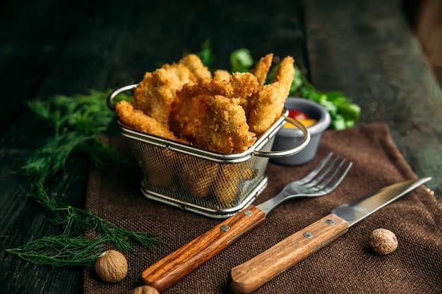 Vista lateral de apetitosas nuggets de pollo frito en cestas de metal sobre una mesa de madera