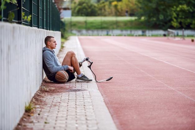 Vista lateral del apuesto hombre discapacitado deportivo serio en ropa deportiva y con pierna artificial sentado en la pista con pelota de baloncesto.
