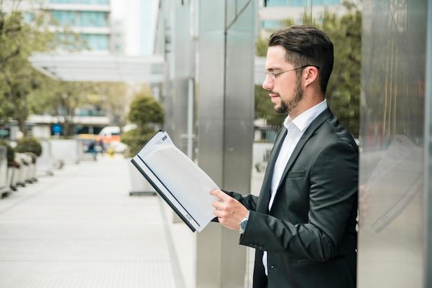 Vista lateral de un apuesto joven empresario de pie contra el documento de lectura de la pared de vidrio