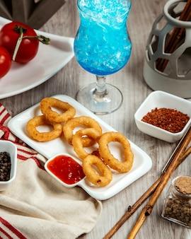 Vista lateral de aros de cebolla frita con salsa picante sobre la mesa