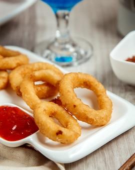 Vista lateral de aros de cebolla frita con salsa de tomate sobre una mesa