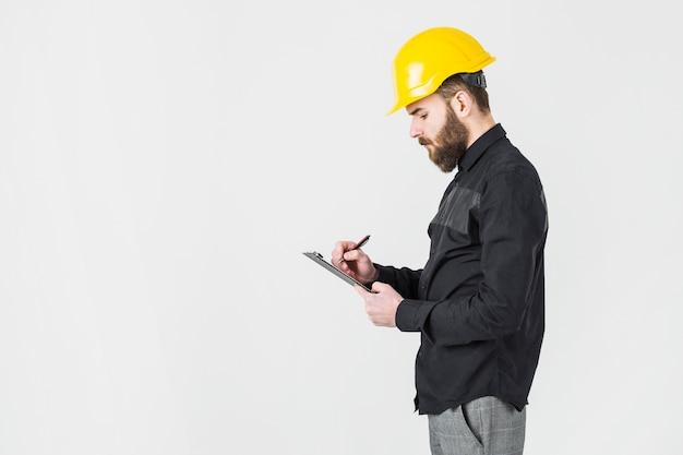 Vista lateral, de, arquitecto de sexo masculino, llevando, hardhat amarillo, escritura, en, portapapeles