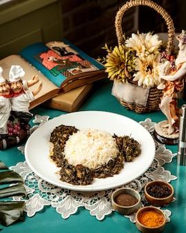Vista lateral de arroz con carne guisada y hierbas en plato blanco
