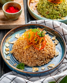 Vista lateral del arroz japonés frito con verduras en salsa de soja en un plato sobre madera