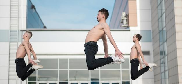 Vista lateral de artistas de hip hop sin camisa posando en el aire mientras bailan