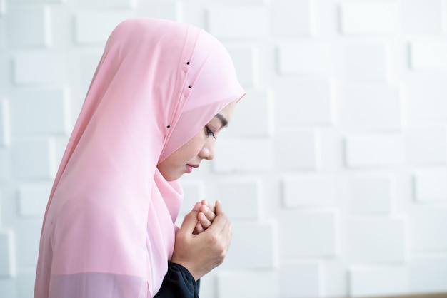 Vista lateral de asia hermosa joven musulmana estudiante mujer oración en hijab rezando sobre alfombra estera en el interior