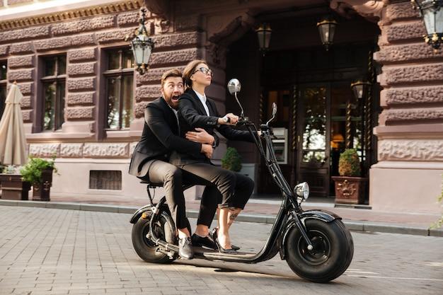 Vista lateral del asustado hombre de negocios con barba monta en moto