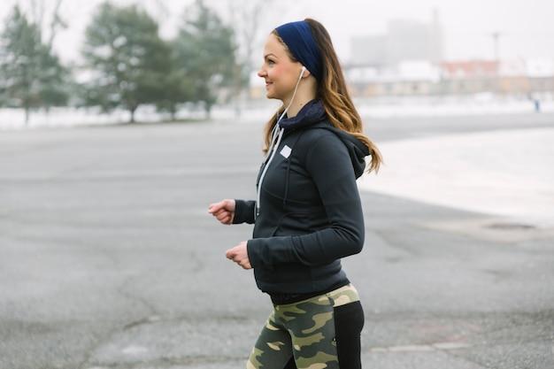 Vista lateral de la atleta femenina corriendo en la calle