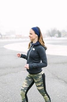 Vista lateral de una atleta femenina haciendo ejercicio en invierno.
