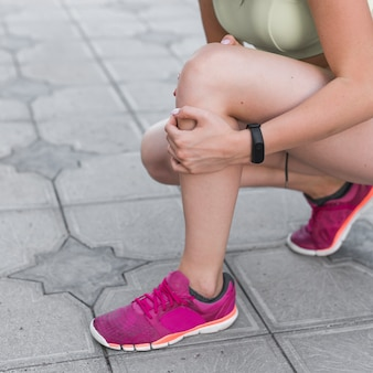Vista lateral de atleta femenina teniendo dolor de rodilla