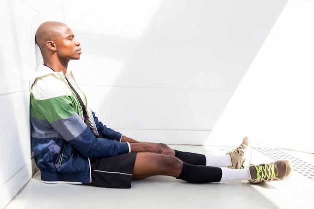 Vista lateral de un atleta masculino joven agotado que se relaja contra la pared blanca