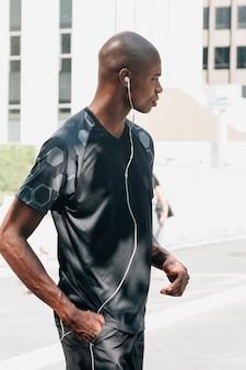 Vista lateral de un atleta masculino joven con la mano en su bolsillo escuchando música en los auriculares