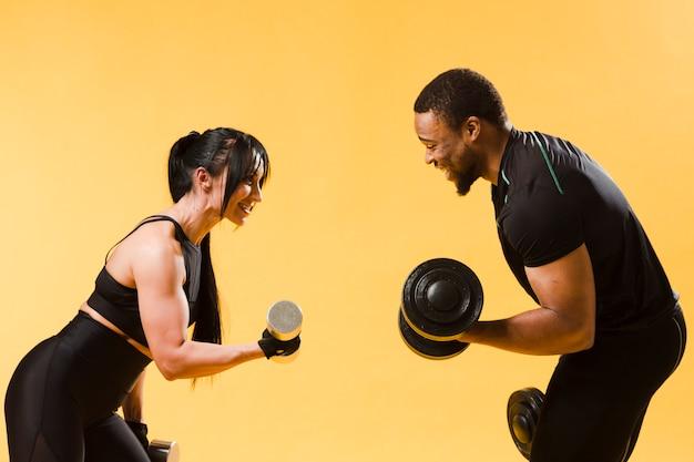 Vista lateral de atletas con pesas
