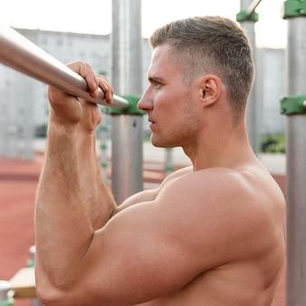 Vista lateral atlético hombre sin camisa entrenamiento